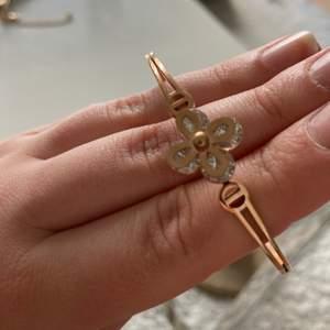 Fint oanvänt armband med silver blomma och koppardetaljer.