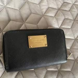 Fin svart plånbok med gulddetaljer. Vet tyvär ej om den är äkta!