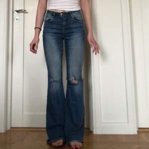 Säljer ett par bootcut jeans men eget gjort hål på höger knä från zara. Har även klippt av lite på längden av jeansen och går ned till marken på mig som är 165 cm. Jeansen är använda men trots det i fint skick. Köparen står för frakten och betalning sker via swish.💞💖