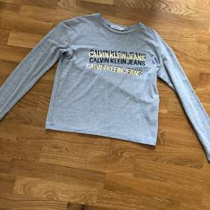 En ny tröja ifrån Calvin Klein som bara är använd 1 gång har inga skavanker. Den är i bomullsmaterial. Strl 12 år = 152