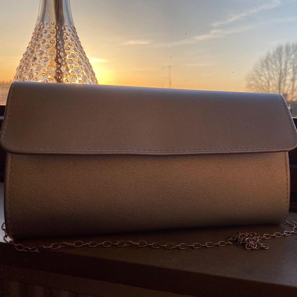 """Silvrig kuvertväska från Anna Field med silvrig stålrem. Beställd från Nelly eller Zalando för 2 år sen, men endast använd en gång. Säljer pga att jag inte använder den. Skulle säga att den är en liten mediumväska, så det finns plats med mycket, men den är fortfarande inte """"för"""" stor. . Väskor."""