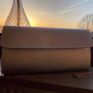 """Silvrig kuvertväska från Anna Field med silvrig stålrem. Beställd från Nelly eller Zalando för 2 år sen, men endast använd en gång. Säljer pga att jag inte använder den. Skulle säga att den är en liten mediumväska, så det finns plats med mycket, men den är fortfarande inte """"för"""" stor."""