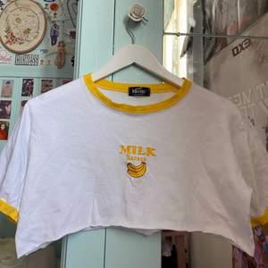 """En jättesöt och snygg croppad T-shirt som jag köpte I Tokyo när jag var där 2017! Kommer från märket Wassup och köpt på Affären """"(Me)"""" ! Texten och banenerna är broderade och passar så bra ihop med det vita och de gula detaljerna på ärmarna och halsen! Frakt ingår i priset💓"""