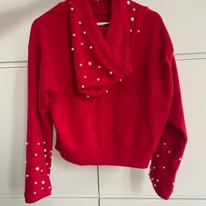 Mysig hoodie från chiquelle i en röd färg med pärlor på luva och armar. Den har en stor mysig luva. Storlek 36