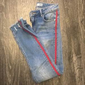 Blåa jeans med rött streck på sidan på båda benen. Hål i en knät. Storlek 26. Kostar 70kr + frakt om du inte kan mötas