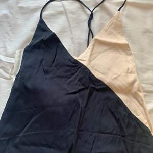 Lång klänning i ljus rosa färg och mörk blå, öppen rygg.