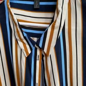 Randig skjorta i vitt, ljus blått, mörk blått och rostfärgad. Längre modell, snygg som oversized eller som en öppen skjorta att ha över.