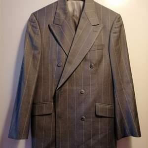 Denna ull kostym är av högsta kvalitén och tillhör Tigers fina Collection. Modellen heter Cassius och är otroligt fin sydd. Design på denna inte bara andas exklusivitet men också känns så när man har på sig den. Det är grå färg med ljusgrå ränder med dubbel bröstad knäppning och sex knappar. Det är en peaked lapel med flap fickor och dubbla vents. Det 100% ren ull. Använd endast ett fåtal gånger så både kavaj och byxor är i absolut nyskick.  Kostar ny i butik: 6750:- / Säljes för endast: 550:-