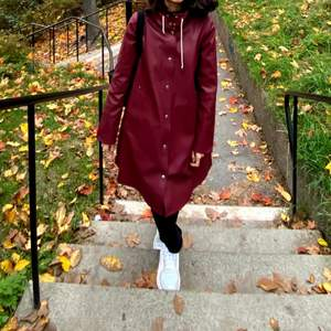 New Stutterheim Raincoat without any harm. I only wore it twice.  The color is burgundy and it is made of waterproof fabric.