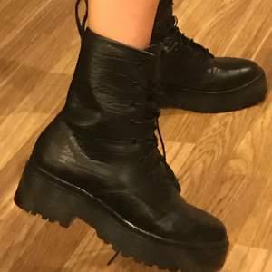 Svarta boots med ormskinns mönster i storlek 37 från Nelly🖤🐍 Aldrig använda utomhus och i bra skick, som nya! Pris kan diskuteras och fraktkostnad kan variera! Skriv vid frågor😇💞