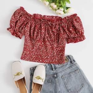 En röd söt sommartopp med blommor på och knytning dör fram, den har en dragkedja på sidan som gör att man lättare kan få på sig den. (Tajt i armarna)