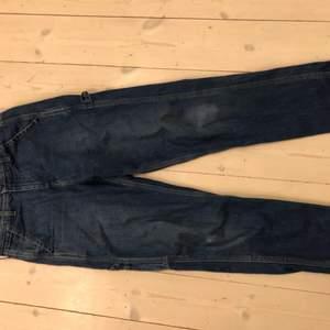 Mörkblå Lee carpenter workwear jeans med fickor på benet samt en flärp att hänga hammare på, måste dock inte användas för just det men ser snyggt ut ;) höger ficka lite trasig (knappt synligt) samt lite uppskrapat på höger knä för mer info och bilder kontakta mig gärna!