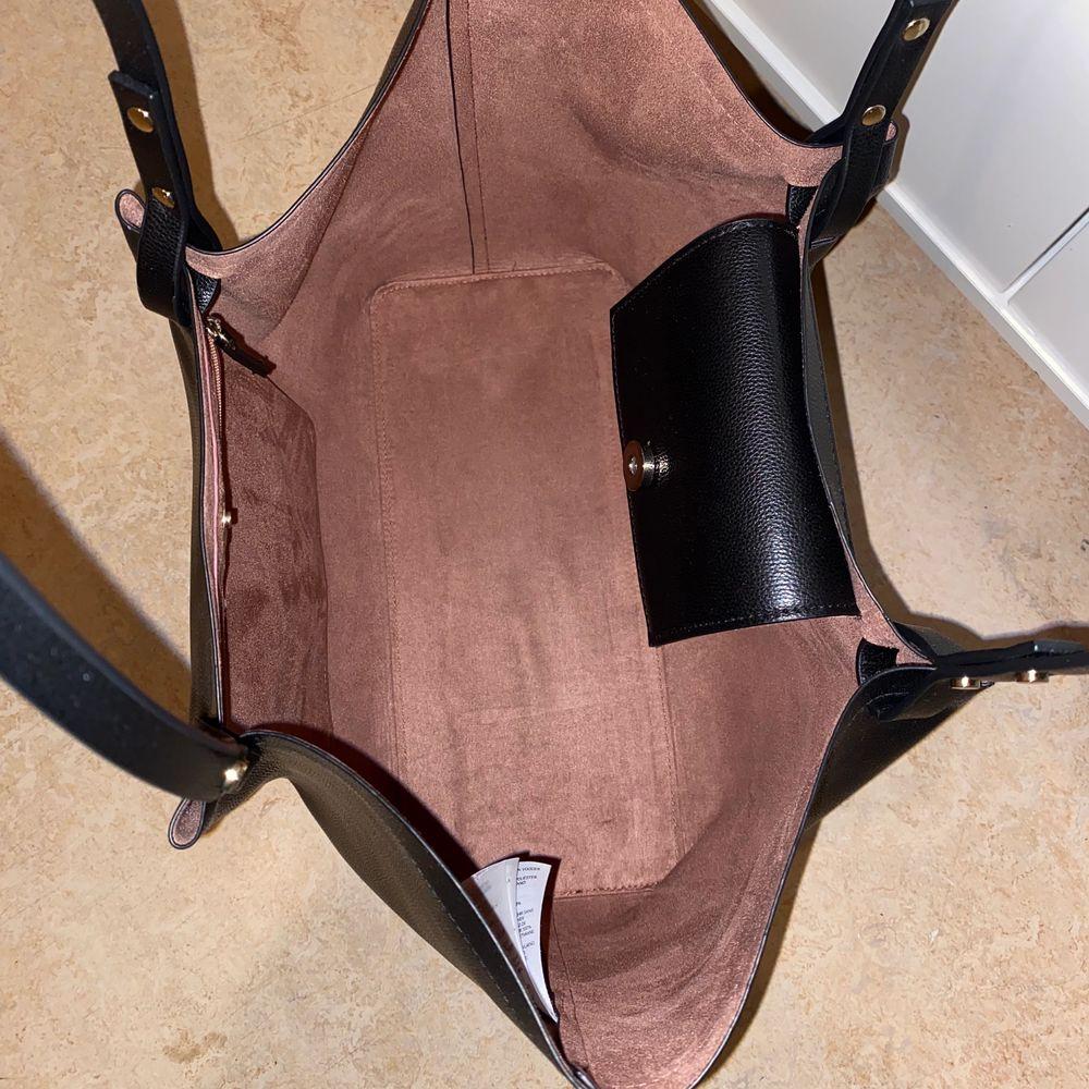 Svart shopperväska från H&M, smuts rosa på insidan med en liten ficka. Frakt är inräknat i priset😊. Väskor.