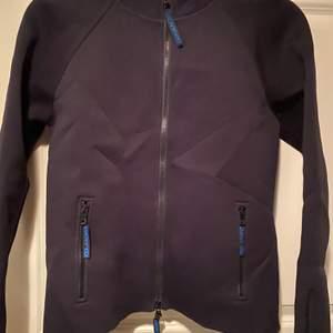 DKNY jacka i dykardräkts material. Svart med tryck på ryggen. Köpt i London, väldigt snygg och speciell. Åtsittande modell märkt XL men tycker den är mer som M. Jag på bilden har XS