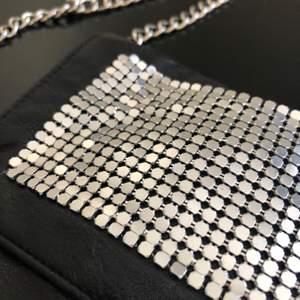 En svart liten axelväska men långt silvrigt kedjeband, använd men fint skick, någon silverplupp på framsidan som lossnat i hörnen på väskan men inget som syns :) köparen står för frakt 🦋