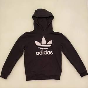 En svart Adidas originals hoodie i storlek 152. Hoodien har tyvärr ett igensytt hål på undersidan av den vänstra ärmen men är övrigt i gott skick. Hoodien funkar för både tjejer och killar. Den kan skickas eller mötas upp i linköping.