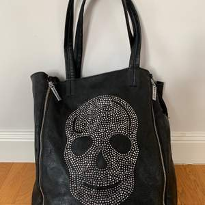 """Rymlig väska med """"döskalle-bling"""". Passar perfekt på axeln. Bredd 37 cm, höjd 35 cm."""