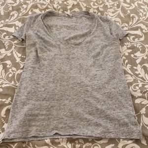 En grå t-shirt med v-ringning, xs men väldigt stor i storlek
