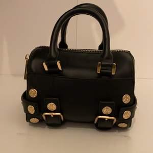 En mindre svart bowler väska med guld detaljer från Topshop. Det finns ett ytterfack, samt en korthållare i huvudfacket. Är i topp skick! B:14L:20H:14 (cm)