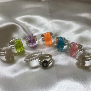 Utförsäljning på ringar! Dessa ringar är justerbara så dom passar allas fingrar. Det finns cirka: 1st blå gummibjörn, 1st grön gummibjörn, 1st orange gummibjörn,1st rosa gummibjörn, 1st lila gummibjörn, 2st vita gummibjörnar, 1st smiley och 1st vit pärlorna med elastisk tråd. Frakt tillkommer på 12kr.