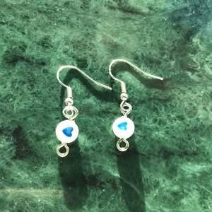 Ett par örhängen som har en pärla med ett mörkblått hjärta på sig!!