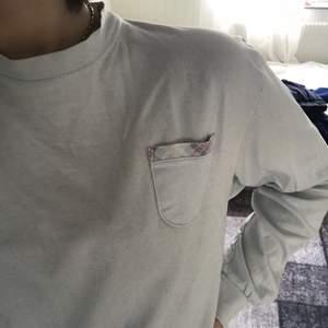 En väldigt ljusblå longsleeve med en ficka på vänster sida🌻 den är lite småsliten i ärmarna