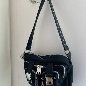 En väska från märket NuNoo, modellen heter Ellie Scuba.  Jag köpte den för 900kr men säljer den för 500:- då den är i nyskick och använts vid två tillfällen.  - axelrem medföljer som syns på bilden - två fack på insidan ena med dragkedja -tre fack på utsidan med dragkedja  Bredd: 24,5 cm Höjd: 15 cm Djup: 8 cm