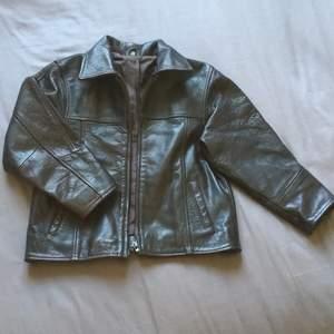 80's skinnjacka i mörkbrunt läder med korta armar!  Det stor XXL på jackan men är en XS:)