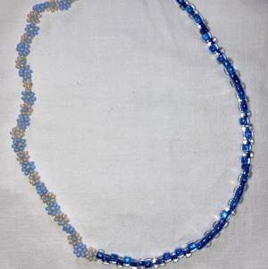Modernt och populärt pärlat halsband, halva sidan med blåa och vita blommor och andra sidan med blåa japanska glaspärlor. Se gärna mina andra annonser för fler halsband och ringar.