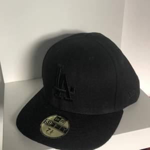Säljer en fitted cap i hel svart. I storlek 7 5/8 och motsvarar 60.5 cm. Aldrig använd. Orginal pris 449kr