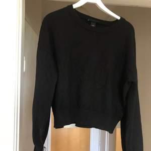 En svart stickad tröja med ballongärm från Monki!