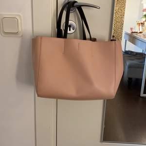 Super fin rosa / aprikosväska med både handtag som man kan hålla i och en axelrem men den går även att ta bort har även ett innefattar man kan lägga grejer som är loss tagit bort från Pull & bear