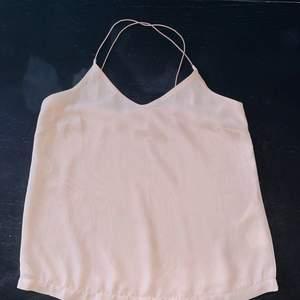 Rosa tunt linne från Vero Moda, använd en gång. Tunt material och korsade snören i ryggen. Lite V-ringad fram och tunna axelband.