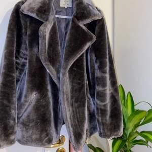 En fin faux fur coat i grå, storlek M. Den är lite oversize och sitter bra (Kan passa storlek L också). Den är inte använd många gånger men en bit av tyget på insidan har rivits upp. Det syns inte när man har på sig den och går lätt att sy upp. Annars är jackan i bra skick, skulle nog säga att jackan är ganska varm. Den passar till hösten men det skulle kunna funka även på vintern om man har något tjockt under.