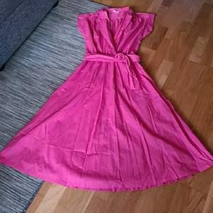 Super vacker klänning från 50talet. Slimmad upptill och klockad kjol, vringad med bälte i midjan, storlek 36. Använd men i topp skick. Bud från 200kr +frakt