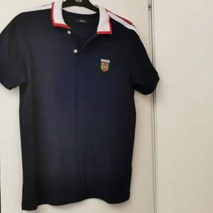En mörkblå Gucci T-shirt. Gucci T-shirt gjord i Italien. T-shirten har används ett par gånger men inte mycket. Den har storleken L och märket GUCCI på ärmen och på bröstet.