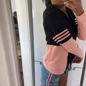 En addidas tjocktröja +luva med färger rosa och svart. Storleken S men är för liten för mig så passar lika bra som Xs