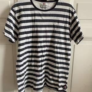 Randig T-shirt från The Defender. Herrmodell i strl L. Passar dock som en oversized S/M på mig. Använd endast 1-2 ggr.