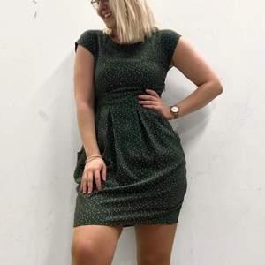 Grön prickig klänning med fickor. Figursydd upptill och lite lösare nedtill. Superfin på! Använd 2-3 gånger. Fler bilder kan tas vid önskemål. Frakt tillkommer.