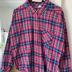 Blå & rosa rutig skjorta från H&M. Lite mer av en cirkel skuren form än helt rak som en vanlig skjorta, och lite batwing ärm. Använd en del men i gott skick