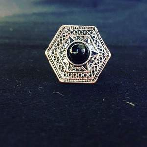 The hexagon, the symbol of resistance and endurance, is the most used and loved shape of nature from honeycomb to snow crystal.  Brass case ring consists of two intertwined hexagonal bezels. Inside the first frame, there are six circle figures on each side. In the second frame there is a six-pointed star motif.  In the middle is the black tourmaline stone, which is believed to take away negative energy and is a powerful guard stone. There are plant motifs on both sides of the finger hoop of the ring. A rare ring that will live for generations, carefully crafted with fine steel pencil work.  Weight: 10 gr Ring size: 10 (16mm inner diameter).   https://youtu.be/l4UEt0vE0WA