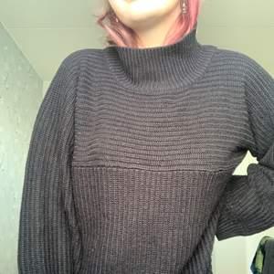 En svart tjocktröja med en högre krage och luftiga armar. Bra skick