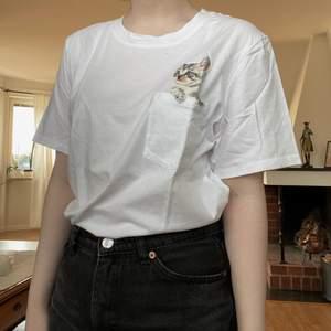 En söt t-shirt från H&M med en katt i bröstfickan! Frakt 45 kr 🌿 Finns i Västerås och tillfälligt Malung.