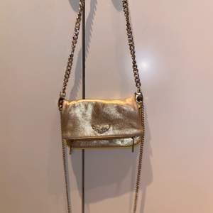 Jag säljer denna guldiga Zadig väska! Rätt så andvänd men funkar fortfarande💕 kommer med 2 olika väskband! Köptes för 2500kr
