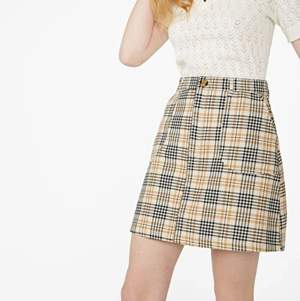 tan and black plaid tartan skirt with a zip on the front and pockets!!! worn only a few times, in basically new condition