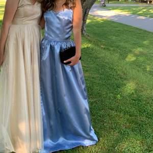 Säljer min blåa balklänning i satintyg. Endast använd en gång. Klänningen är sydd på min efterfrågan så den kommer inte från något märke💙med öppen rygg och kors-snörning. Har en slits på sidan. Skicka meddelande för fler bilder! (Jag är 165 cm lång)