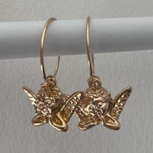 guldiga örhängen med söta änglar💞💞 aldrig använda!