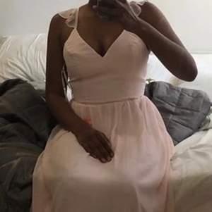 Denna fina klänning är något för människor med längre figur, Själv är jag 172.  klänningen är ljusrosa med volanger på axlarna som framhäver bysten. Den går även in i midjan. !!Finns några fläckar på den som går bort i tvätten!! Använd en gång. Köpt för 1200kr. Säljer för 150kr. Avhämtning, annars shippnig som DU står för eftersom att priset är så billigt❤️  passar M/S