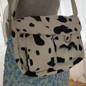 Söt väska med ko-mönster. Många småfickor och i fint skick! Köpare står för frakt💕