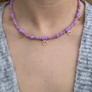 Lila pärlhalsband med små söta guldhjärtan 💜🥳⭐️🥺 halsbandet försluts med lås och tråden är elastisk
